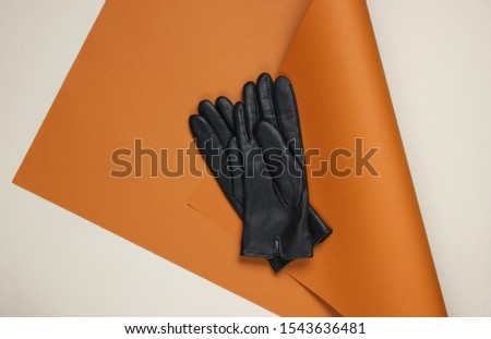 Leather gloves on folded paper background. Minimalistic fashion still life. Flat lay. Top view