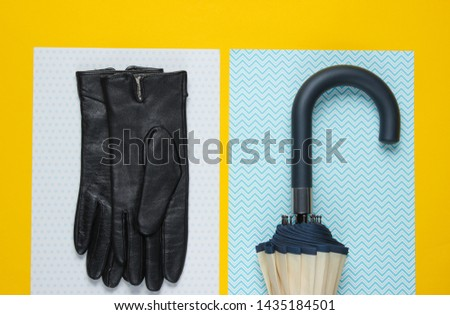 Leather gloves, umbrella hook on a creative yellow background. Top view