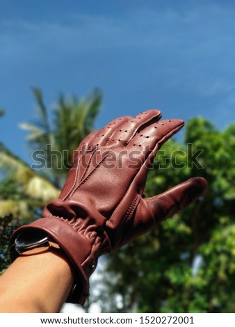 leather gloves with nature blue sky background