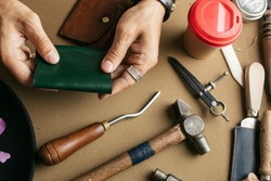 Leather goods master hands and handmade leather wallets lay on table with crafting tools. Workflow in the workshop. Workflow in the workshop, close-up.