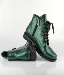 Leather green shoes. Winter shoes. Stylish boot isolated on a white background. Close-up. Laces, tractor sole, comfortable last. Casual style. Boots. Copy space.