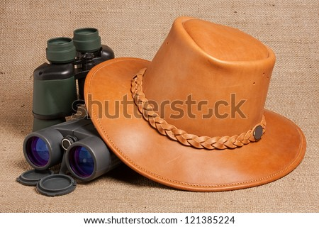 leather hat together with two pairs of binoculars