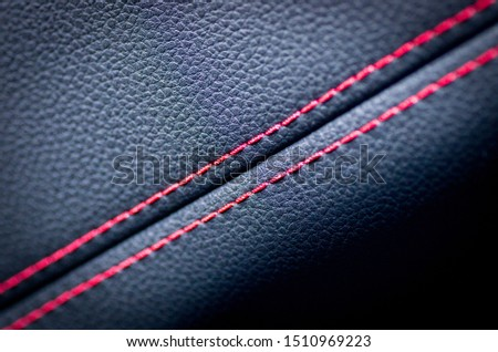 Leather interior of the luxury modern car. Perforated leather comfortable seats with stitching. Modern car interior details. Car detailing. Car inside. Leather texture background.