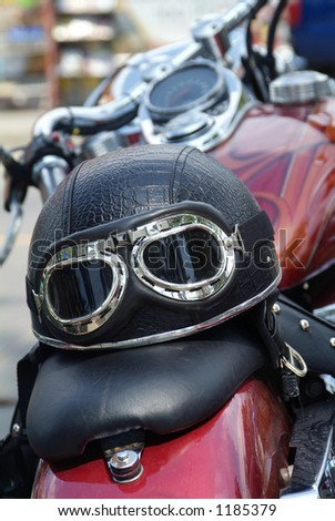 Leather motorcycle helmet with goggles on the seat of traditional, large motorcycle