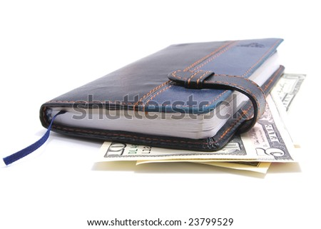 leather notebook laying on american dollars isolated over white background