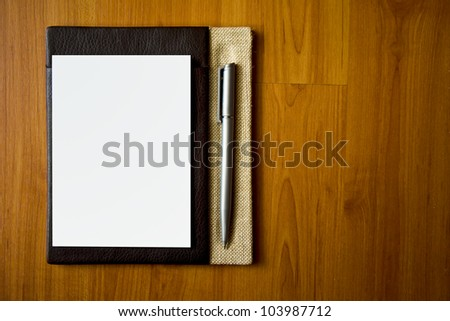 Leather notepad with paper and pen on wood desk