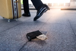 Leather purse with a money and passport lying on the sidewalk and feet of outgoing man