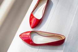 Leather red women's shoes on a white wooden shelf. Fashion, minimal fashion concept, women's shoes, accessories. red women's lacquered leather shoes