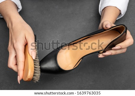 Photo of Leather shoes care concept. Shoe cleaning and polishing background with free copy space. Close up picture of woman hands cleaning shoes