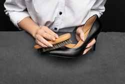 Leather shoes care concept. Shoe cleaning and polishing background with free copy space. Woman hands holding brush for foorwear over dark textured background.