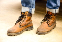 Leather shoes of car mechanic or cowboy. Man's legs dressed in shoes standing on the floor. Young fashion man's legs in blue jeans and brown boots on the  floor.