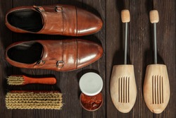 Leather shoes with accessories for cleaning arranged on a wooden board