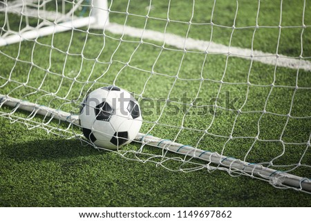 Leather soccer ball in empty gate behind net on green football field