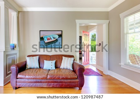 Leather sofa and living room with open door with grey walls.