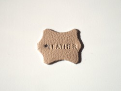 Leather tags or label on white background. Top view. The inscription leather is embossed on the surface of the material. White background, shadow. Manufacture of leather goods. Level of quality.