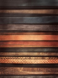Leather textured background - stripes of the straps in classic style. Trendy accessories as backdrop for vertical billboard or fashion magazine cover. Leather belts as horizontal lines for your text.