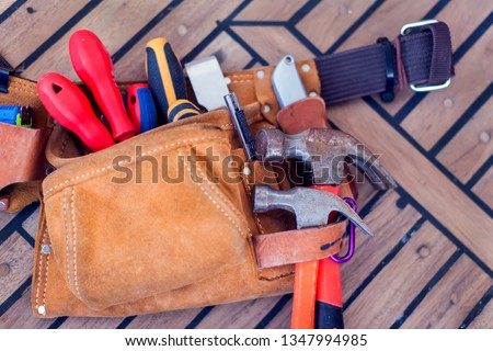 Leather tool belt with construction tooling on wooden board. Maintenance concept.