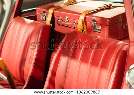 Leather travel suitcase fixed in the car. Interior of luxury vintage car. Active leisure concept.Vintage style