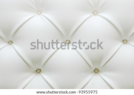 Leather upholstery. White leather with pearl buttons. Background of expensive furniture. The texture of quilted furniture.