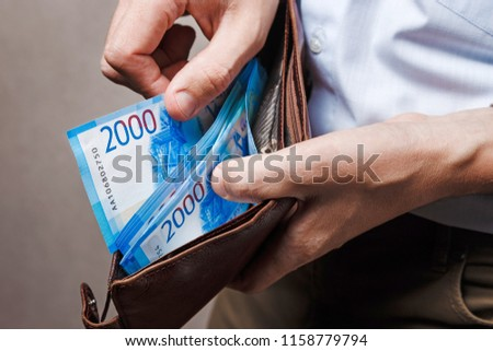 Leather wallet with money in male hands. Russian money, russian cash background. #1158779794