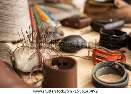 Leather working tools on working desk, bunch of needles, shallow dof #1536143492