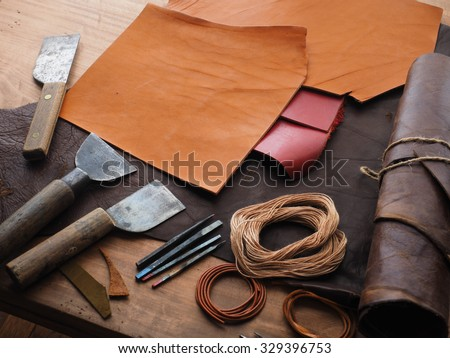 Leathersmith\'s work desk . Pieces of hide and leather working tools on a work table.