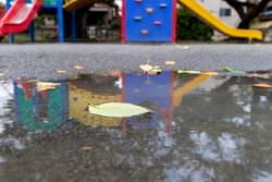 Leaves floating and reflections of plaything in the water puddle of the park after the rain