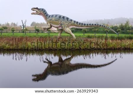 LEBA, POLAND- OCTOBER 01: Dinosaur model in with water reflection in open park in October 01, 2011, in Leba - Poland. Leba Park is 20ha area park in North Poland with original dinosaur models.