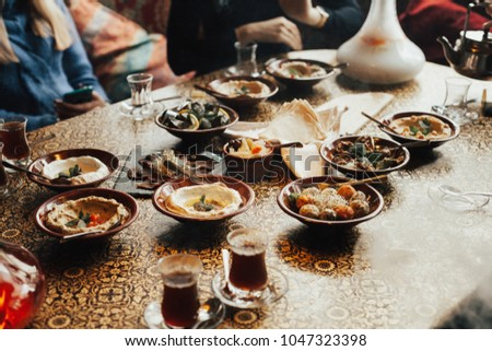 Lebanon cuisine served in restaurant. A young company of people is smoking a hookah and communicating in an oriental restaurant. Traditional meze lunch #1047323398