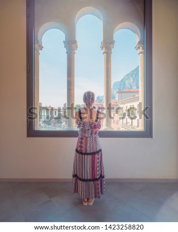 Lecco, Italy - June 21, 2017: a girl starring at the window at the museum Palazzo delle Paure on Lake Como