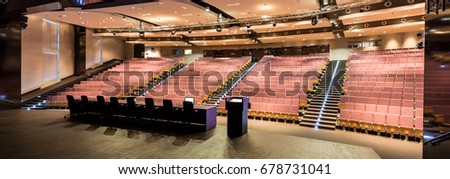 Lecture hall with red seats for thousand students. On the stage desks for teachers