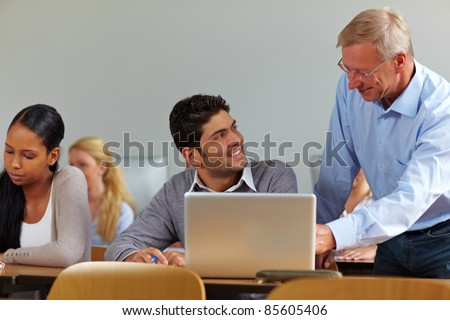 Lecturer talking to student in class at university