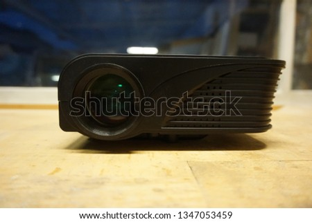 Photo of  LED Beamer in black on a wooden table. View from the front.