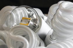 Led bulb among the many CFL lamps in front of black wall