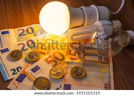 LED bulb on, with fluorescent bulb and incandescent bulb, with bills and coins next to it. Energy costs and evolution of light bulbs.
