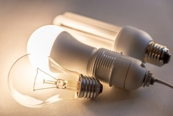 LED bulb on with fuorescent bulb and incandescent bulb next to it. Evolution of light bulbs.