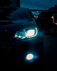 LED car headlight lit in the dark with sparks around and some smoke