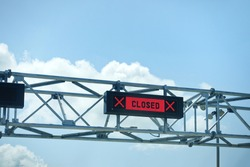 LED closed sign at country border gate against blue sky. Border closed in coronavirus pandemic lockdown to restrict non-essential travel. Multiple countries ban UK travellers due to new covid variant.