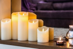 led electric and wax candles stand in the home fireplace. Modern interior of the house