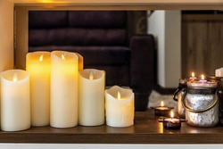 led electric and wax candles stand in the home fireplace. Modern interior of the house. focus on the led electric flame