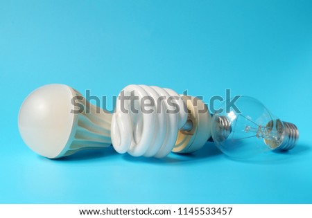 Led lamp, fluorescent lamp and incandescent lamp on blue background. Save on energy and your money with progressive technology.
