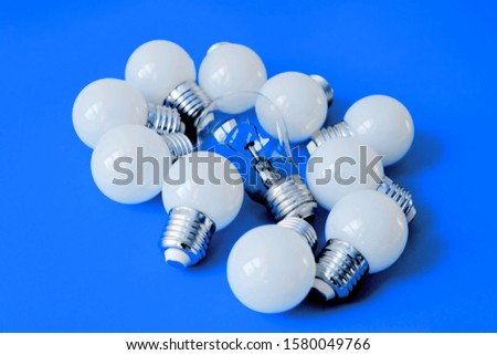 LED lamps on Color of the year 2020 Classic Blue background. Lamps, LED lamps and fluorescent lamps on blue background. White energy-saving light bulbs. Light bulbs lie in a row. #1580049766