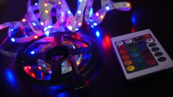LED strip in purple colors and a control panel for switching colors. Dark background
