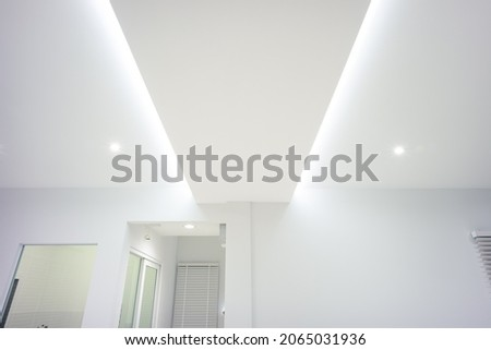 LED strip light and illumination. Also called ribbon light or LED tape to suspended on ceiling in plasterboard in empty living room include down light, white wall. Interior home design and technology.