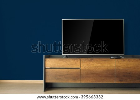 Led TV on TV stand with dark blue wall. led, tv, television, wooden furniture, wood texture, empty room, living room, home decor, blank screen, laminate floor