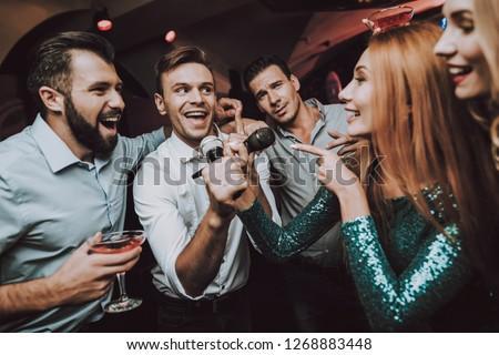 Ledy in Green. Duet. Trendy Nightclub. Have Fun. Dress. Background. Cheerful. Smile. Smiling Girl.Singing Songs. Handsome Men. Beautiful Girls. Friends at Karaoke Club. Karaoke Club. Celebration.
