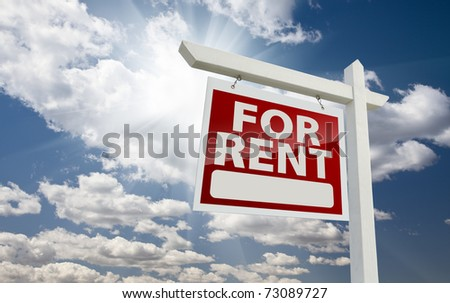 Left Facing For Rent Real Estate Sign Over Clouds and Sunny Sky with Room for Text.