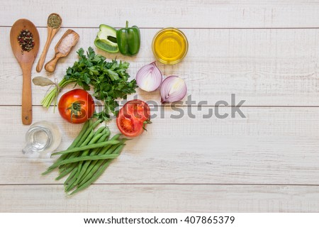 Left fresh vegetables ready to cook tomatoes, peppers, green beans, onions, parsley, spices in wooden spoons on light wood background, right empty space. Vegetables ingredients. Horizontal.Top view.