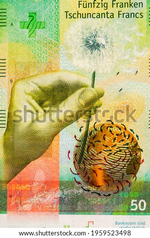 Left hand holding a dandelion with flowing, silky pappi carried forth by the wind. Portrait from Switzerland 50 Francs 2015 Hybrid Polymer Banknotes.