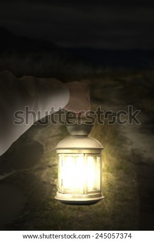 Left hand holding light illuminating dark road at night background